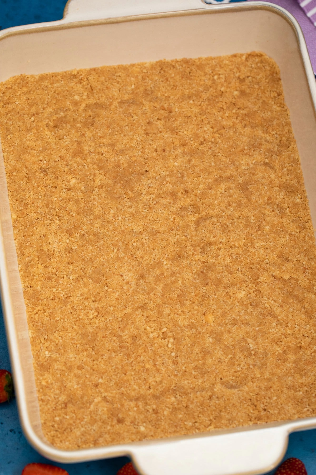 Baking dish with graham cracker crust on counter