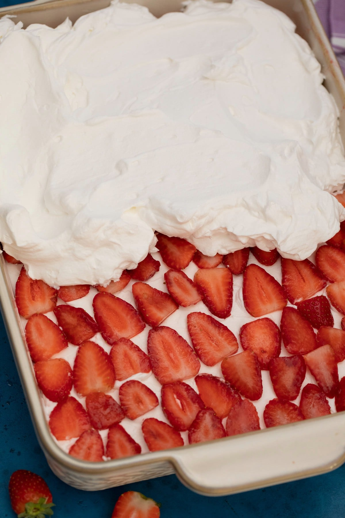 Adding whipped cream over strawberries