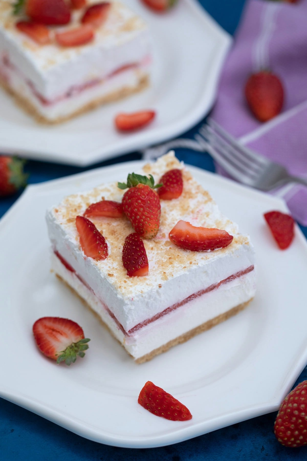 Square slice of strawberry dessert on white plate
