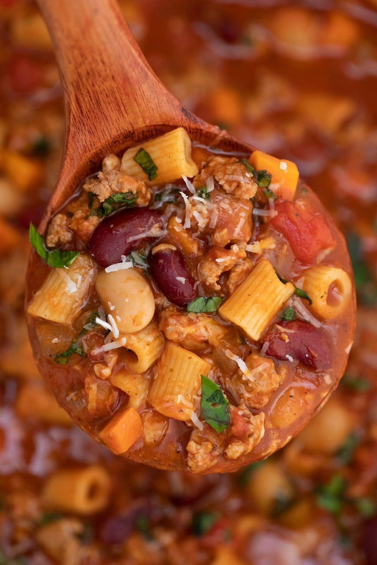Wooden spoon filled with soup with beans and pasta