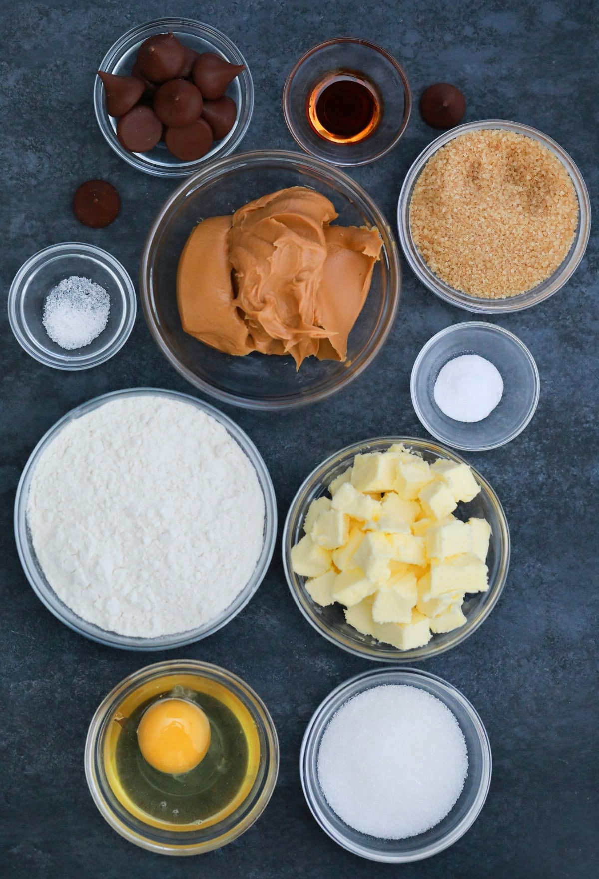 Ingredients for peanut butter blossom cookies in bowls on gray counter