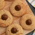 Cookies with Hershey's kisses in center on wooden cutting board