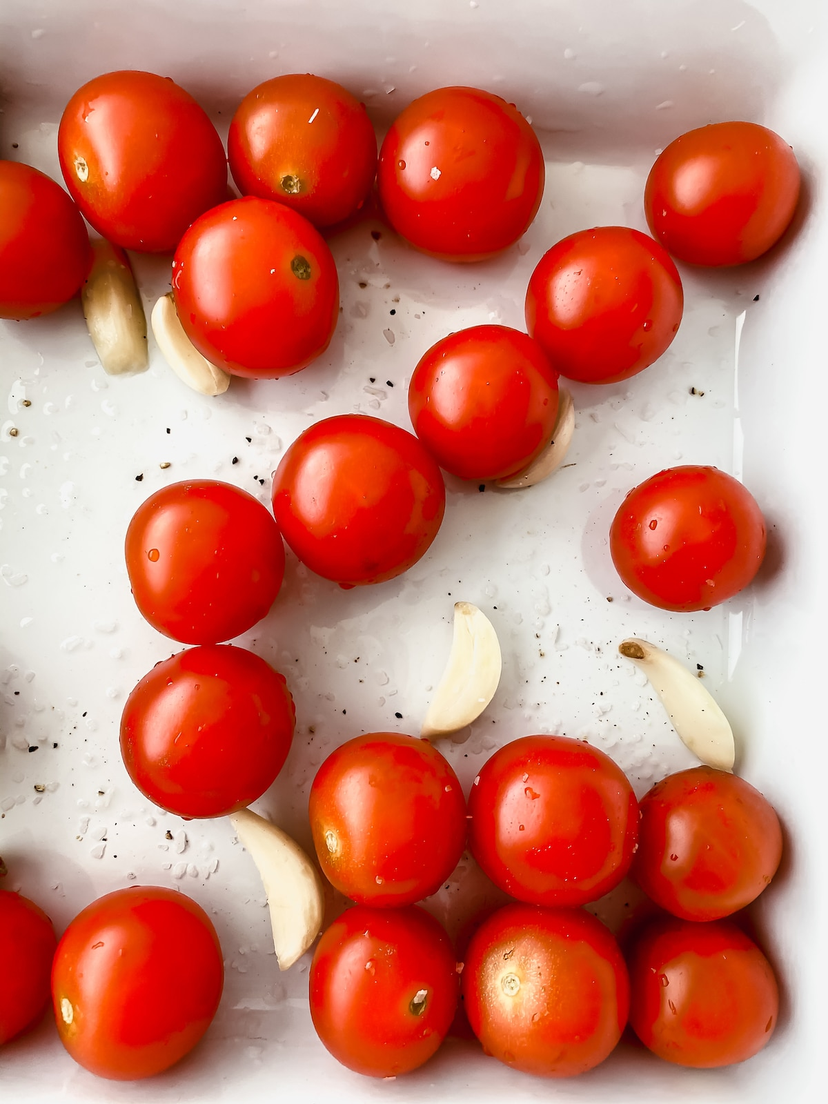 Tomatoes in baking dish with garlic