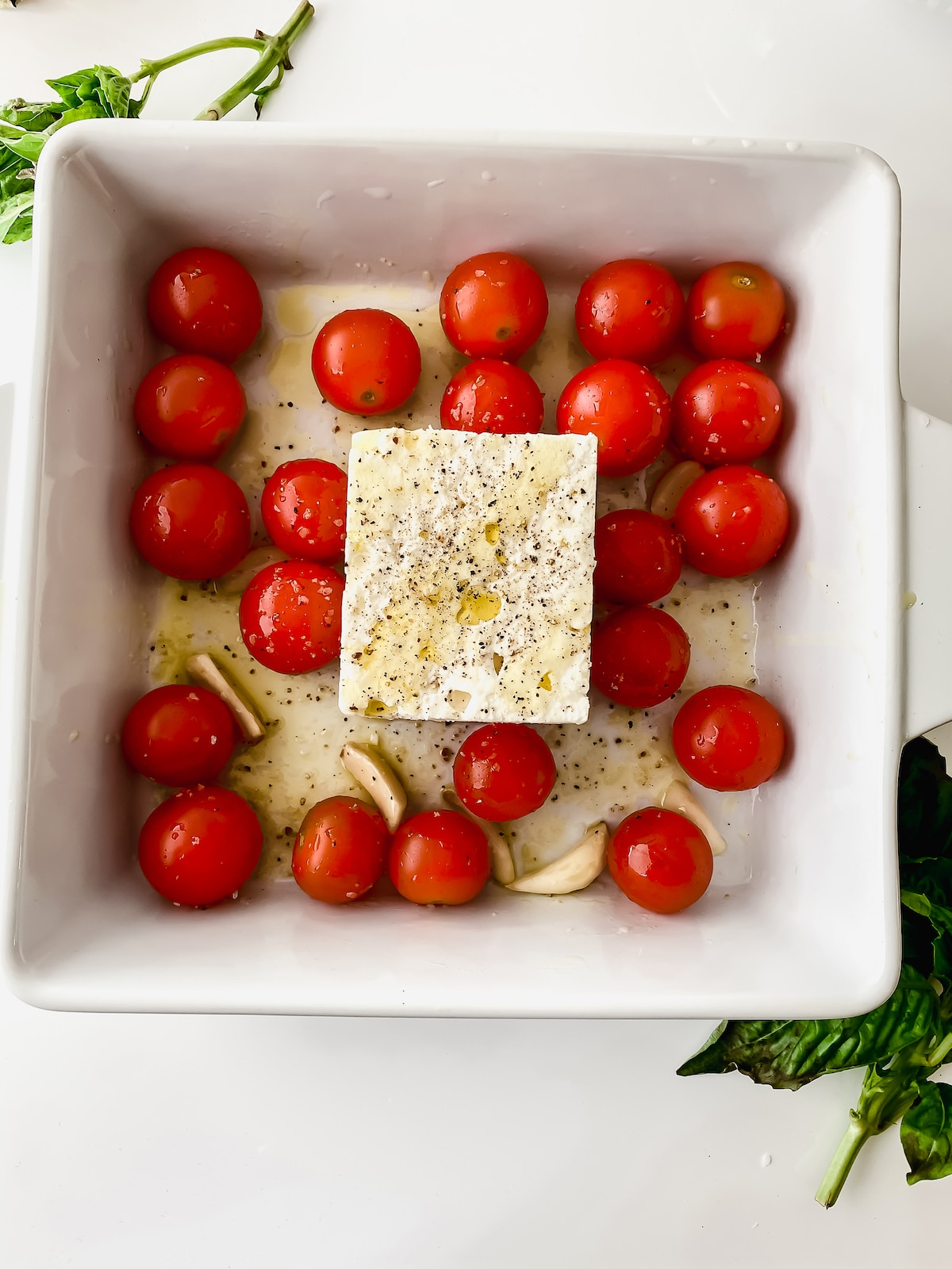 White baking dish with tomatoes and feta