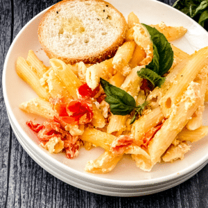 Pasta with basil on top in white bowl