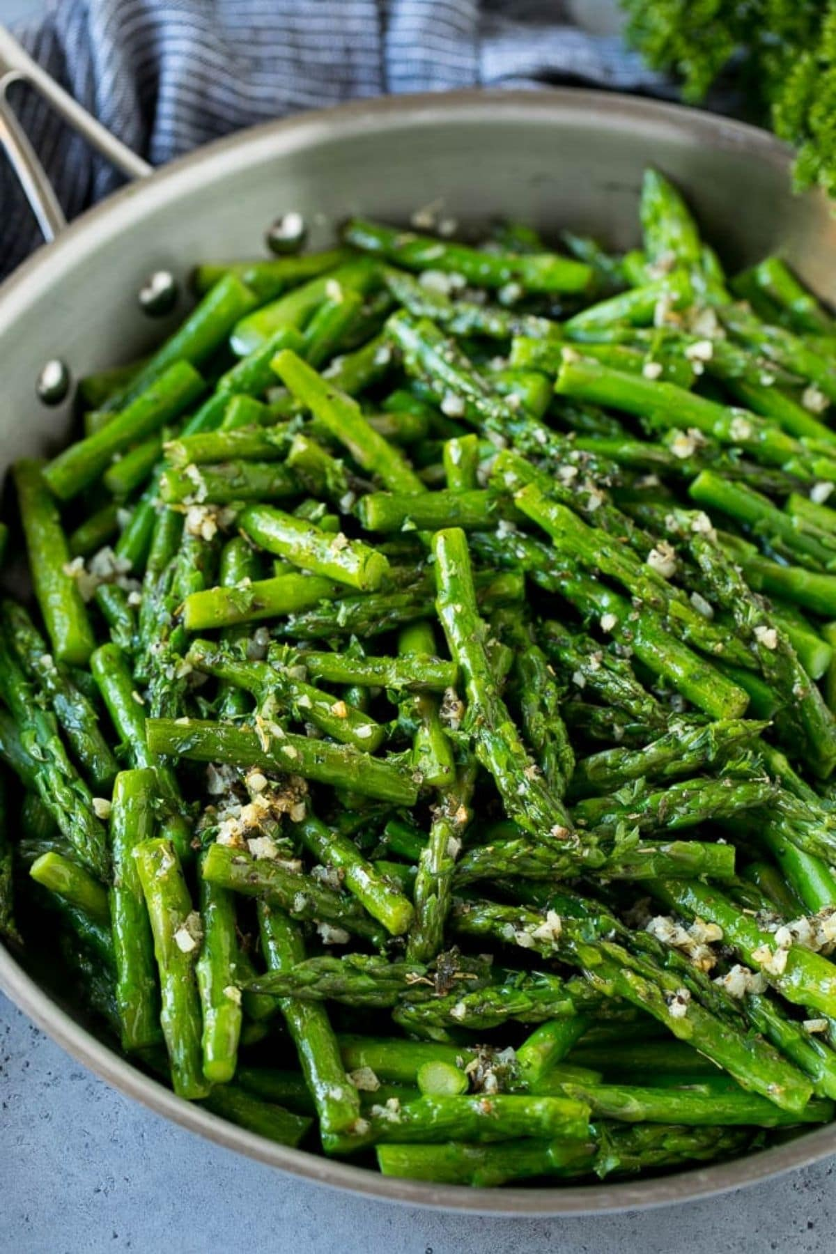 Bright green asparagus heads in skillet