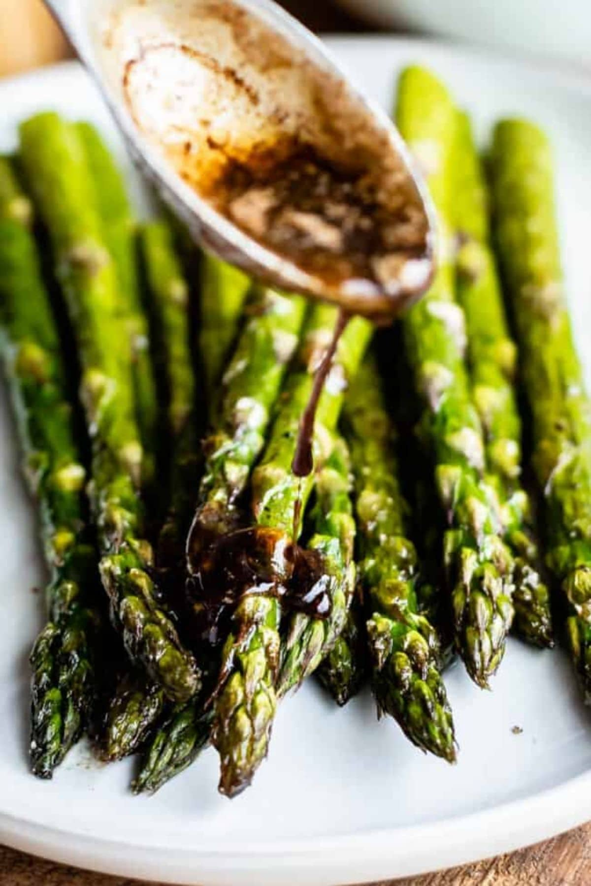 Wooden spoon pouring sauce over stack of asparagus