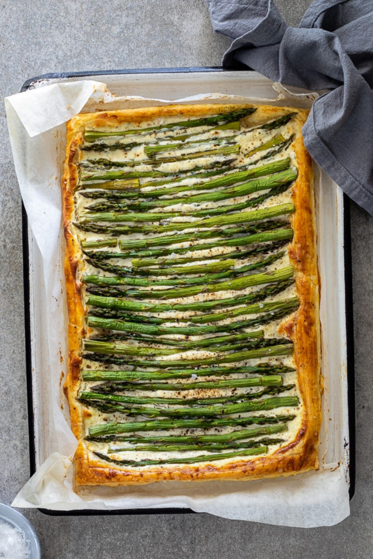 Asparagus tart on parchment paper on baking sheet