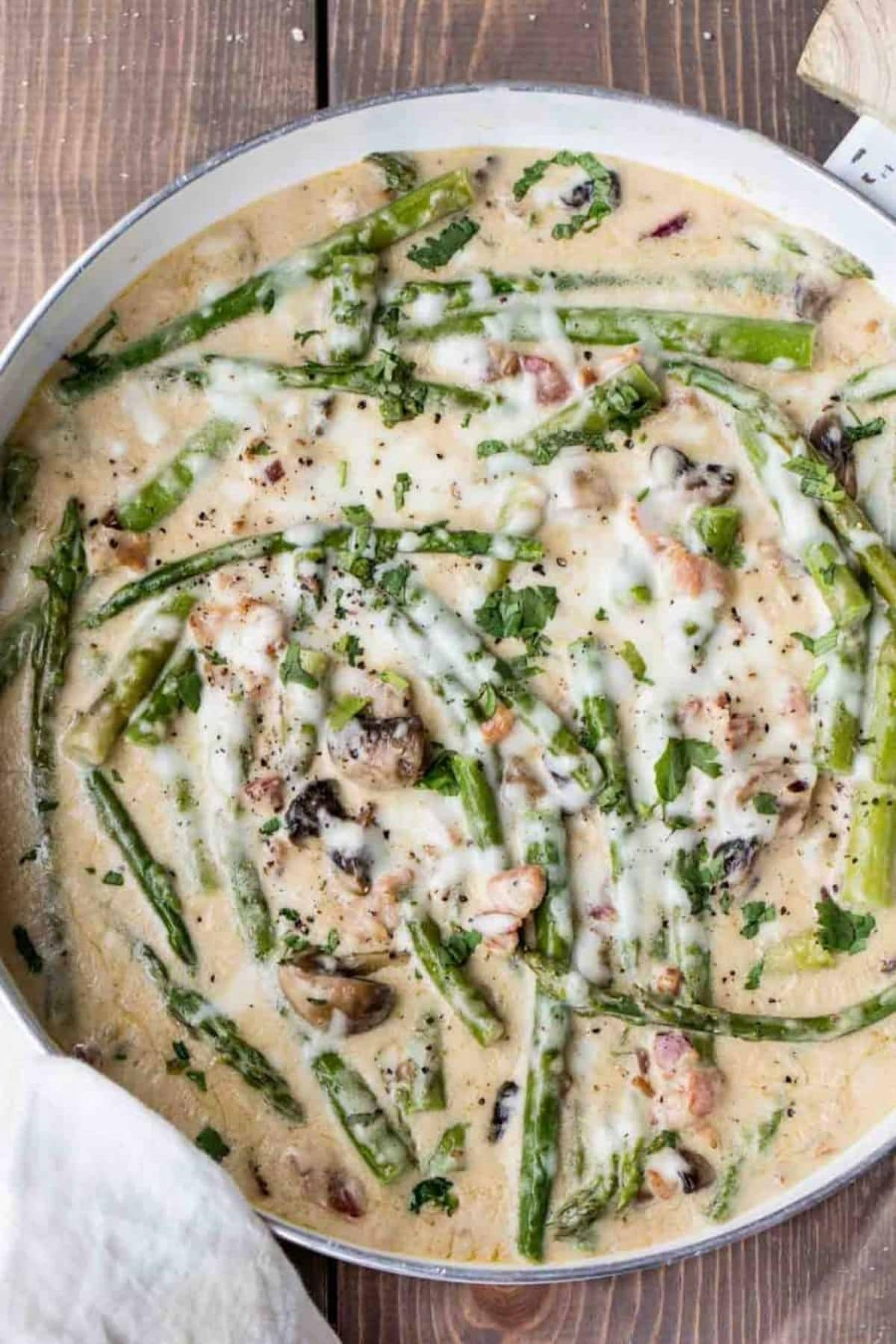 Skillet filled with cream sauce and asparagus