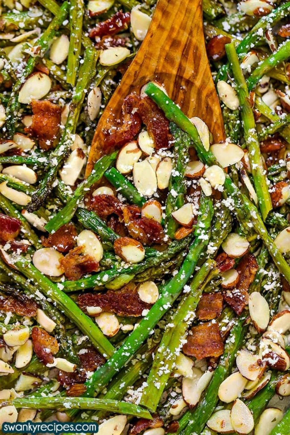 Wooden spoon in asparagus mixture with almonds