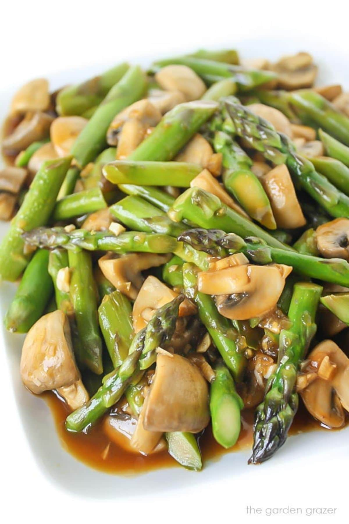 Chicken stir fry with asparagus on white plate