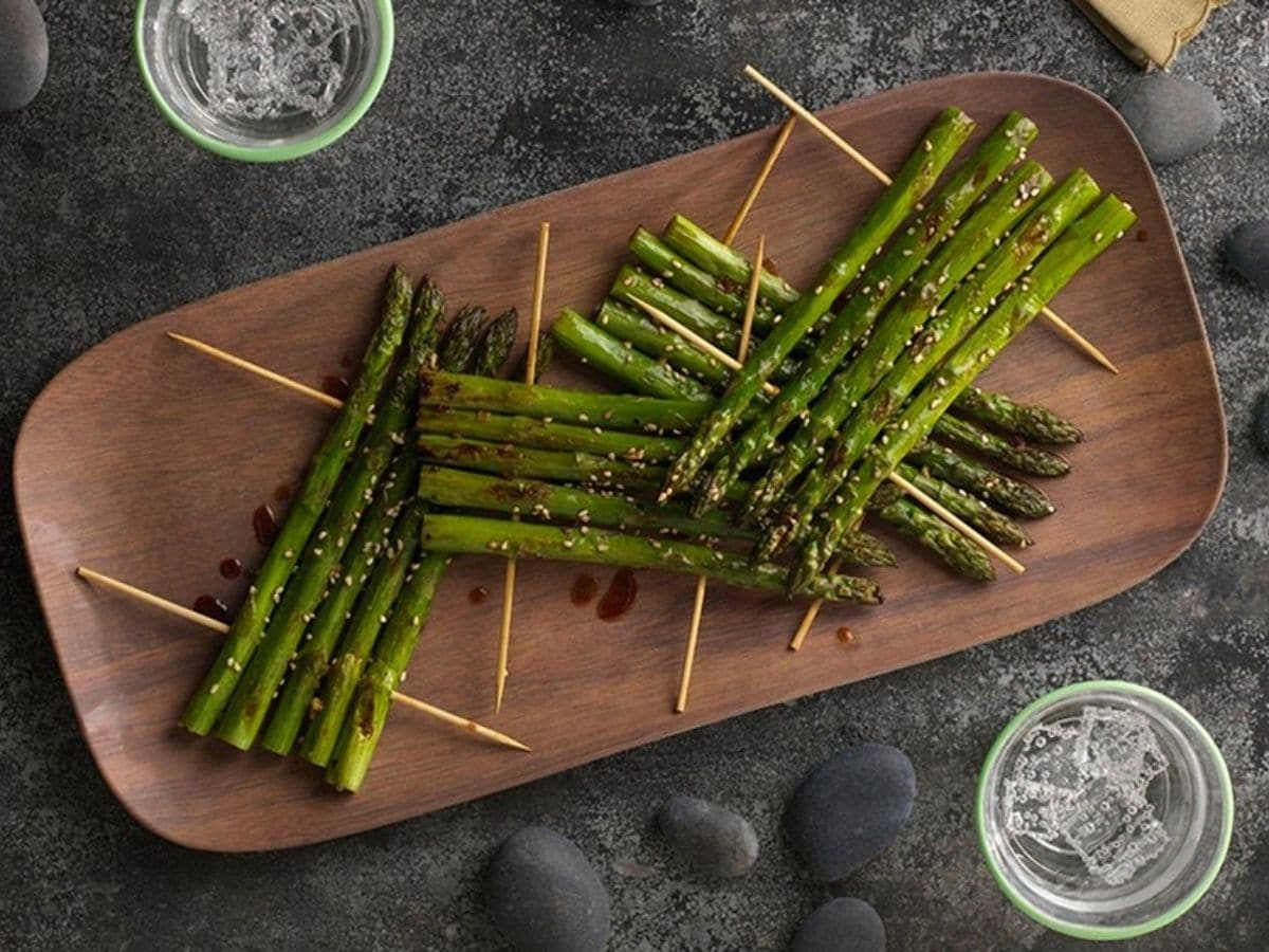 Asparagus spears with skewers on cutting board
