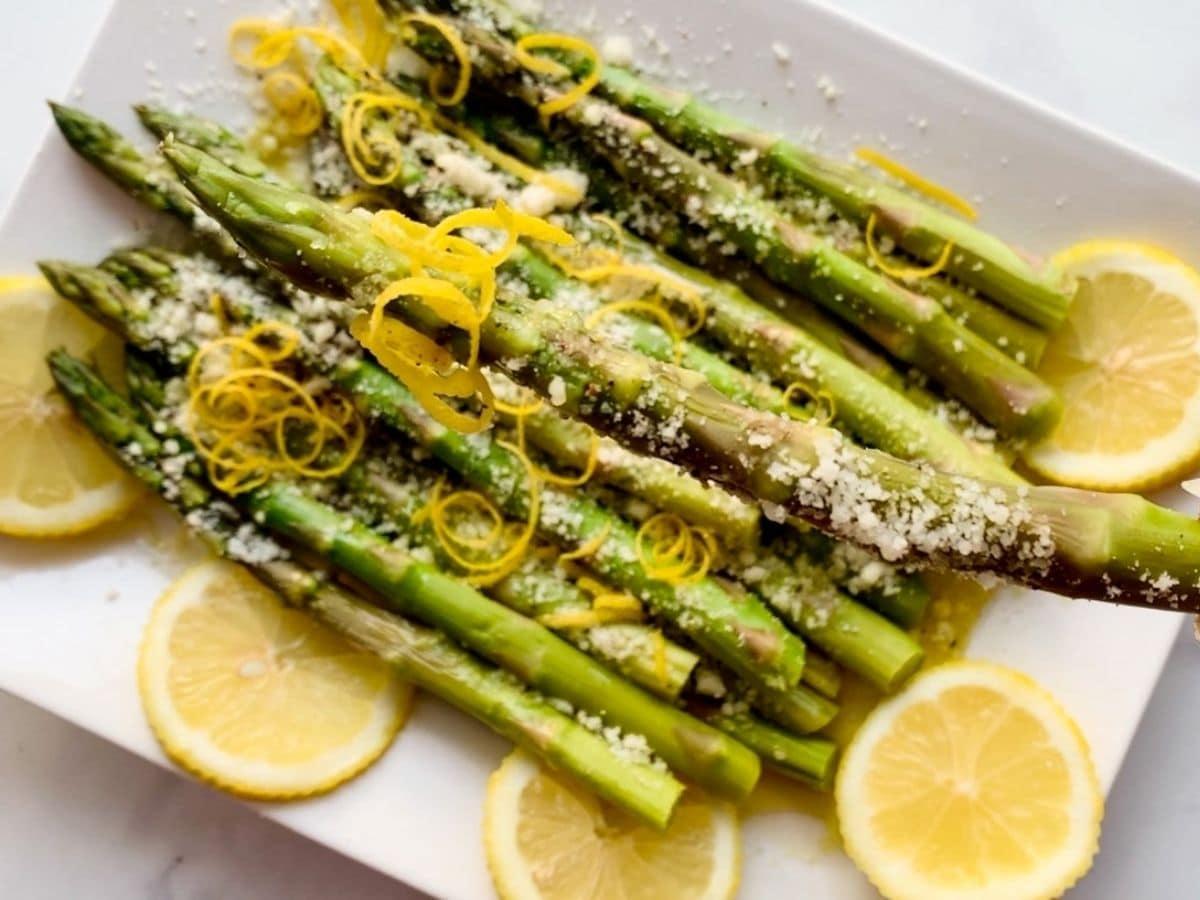 Asparagus with lemon on white platter