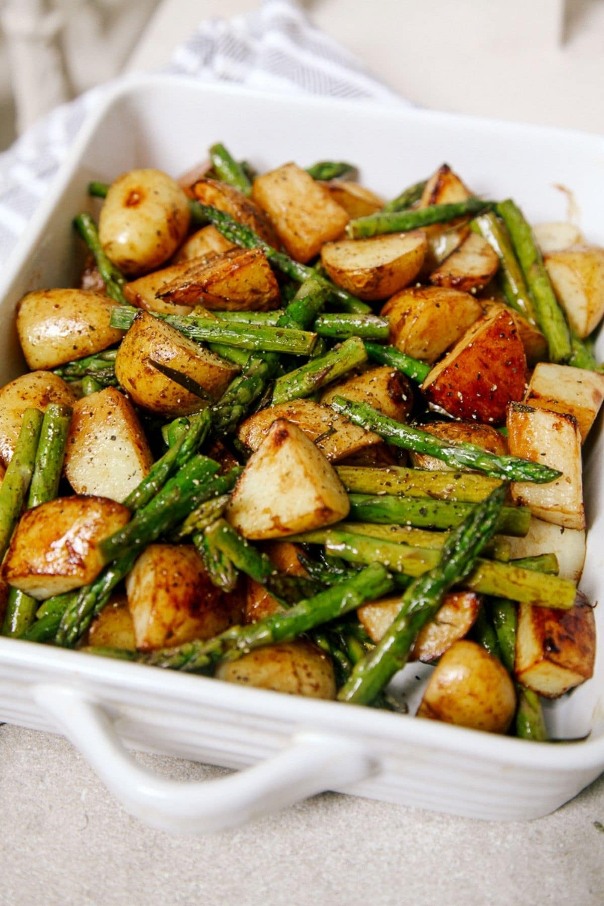 Potatoes and aspargus in white baking dish