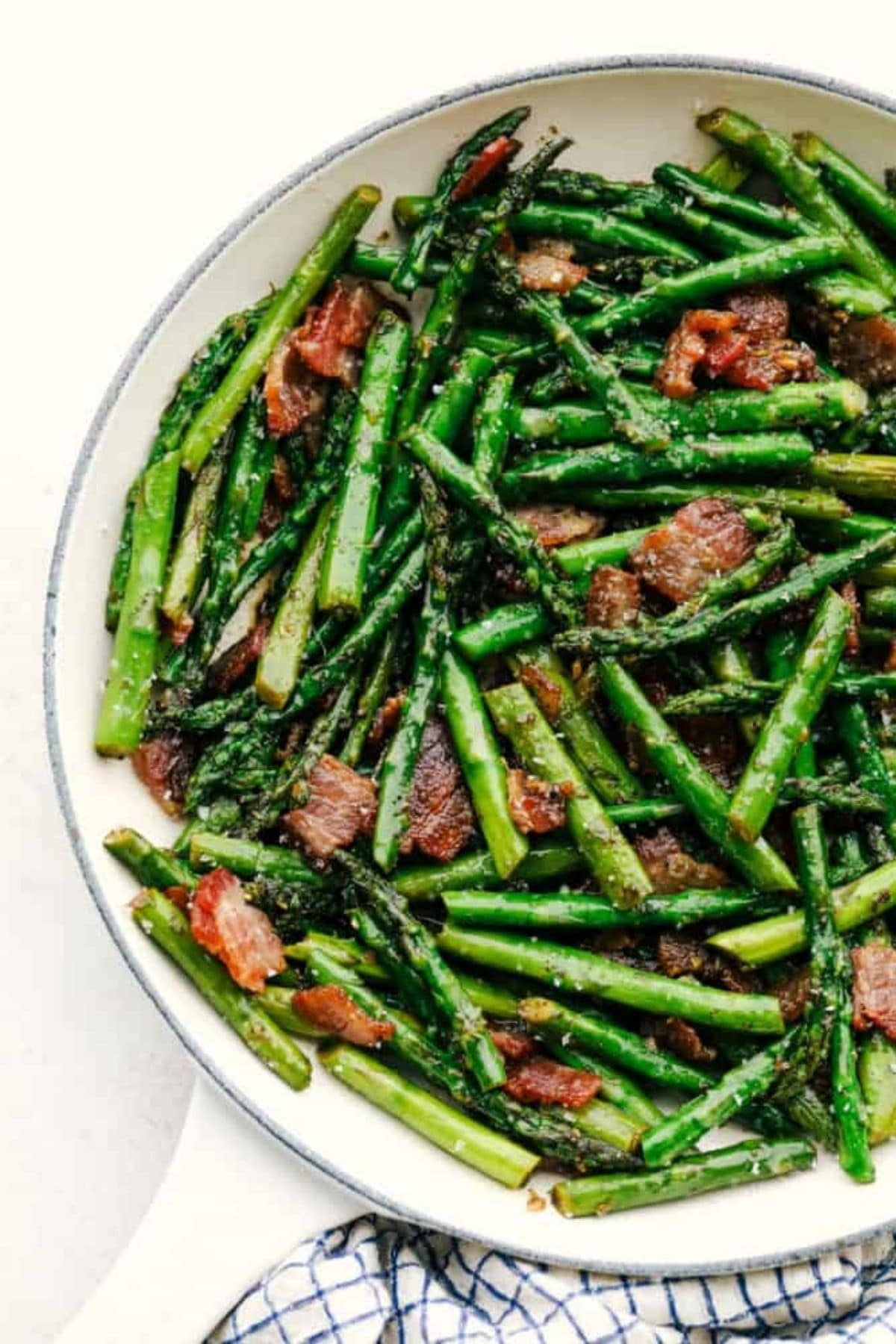 White bowl of asparagus with bacon