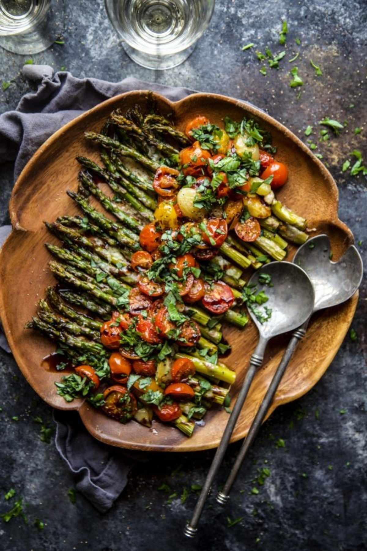 Round wooden plate with asparagus topped with cherry tomatoes