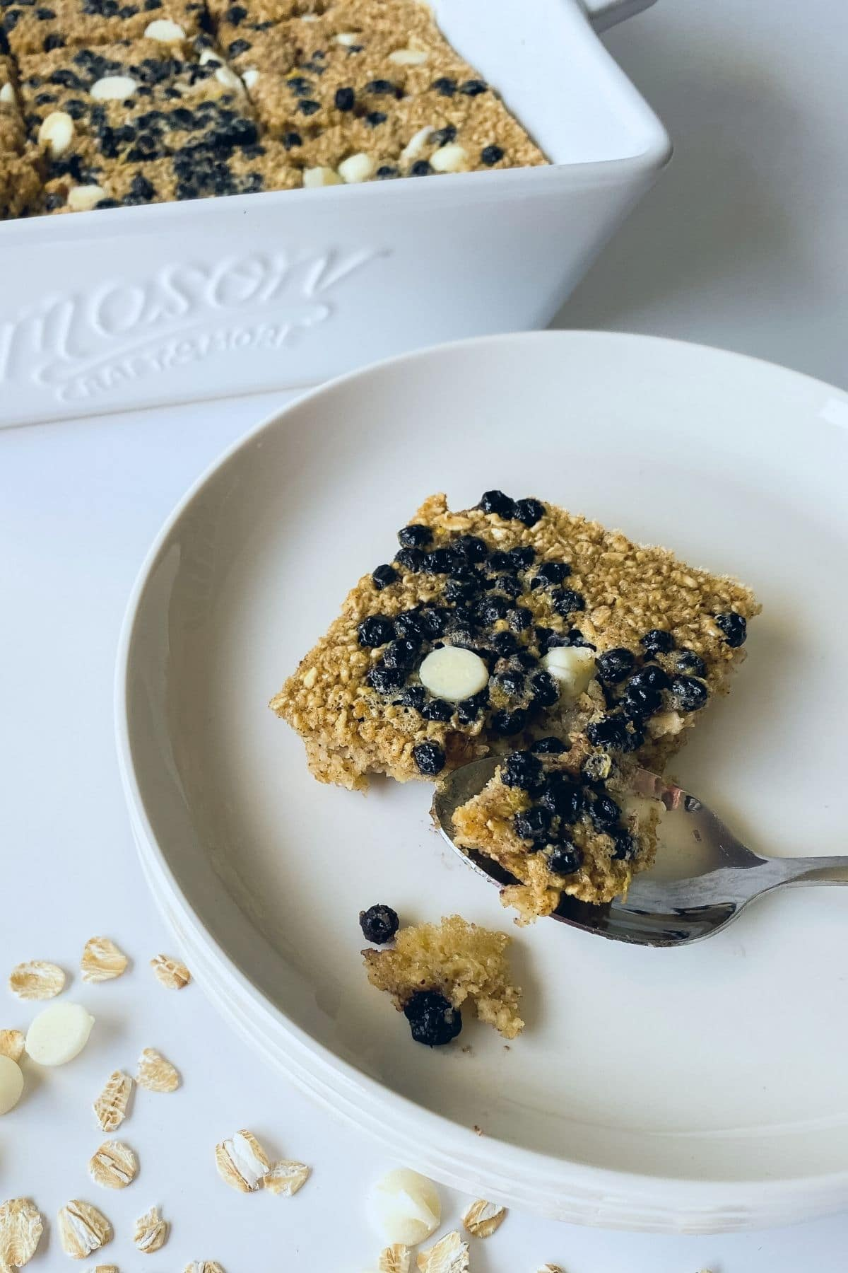 Slice of blueberry oatmeal bar on white plate