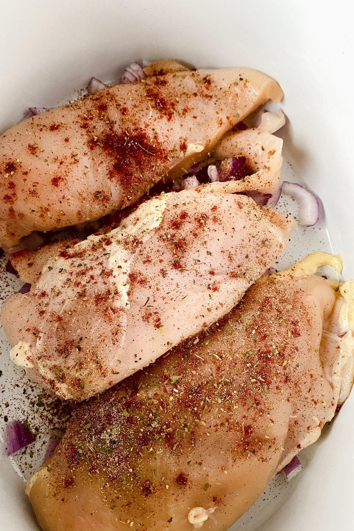 Seasoned chicken in a white slow cooker