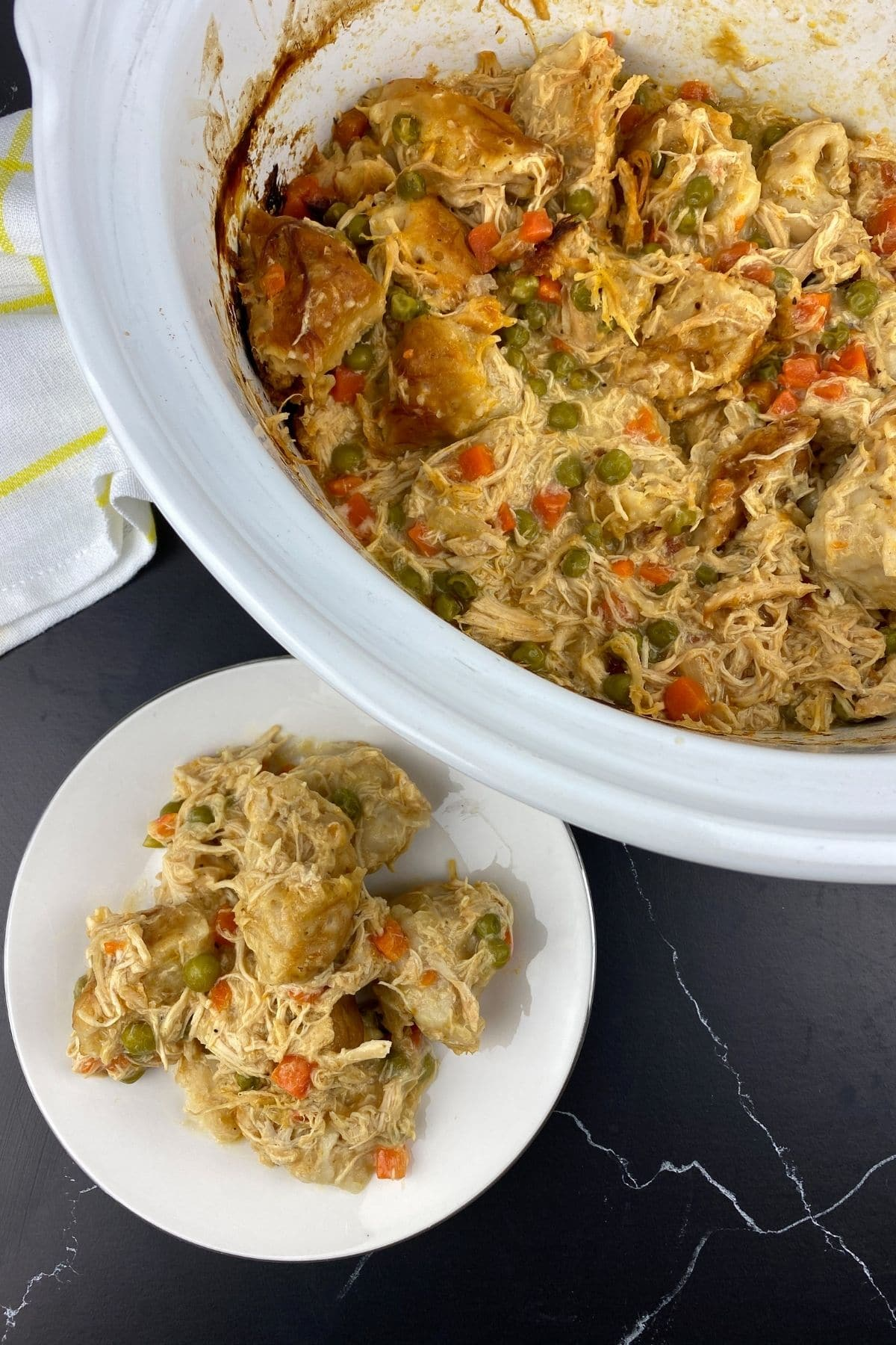 Chicken and dumplings in white slow cooker by plate