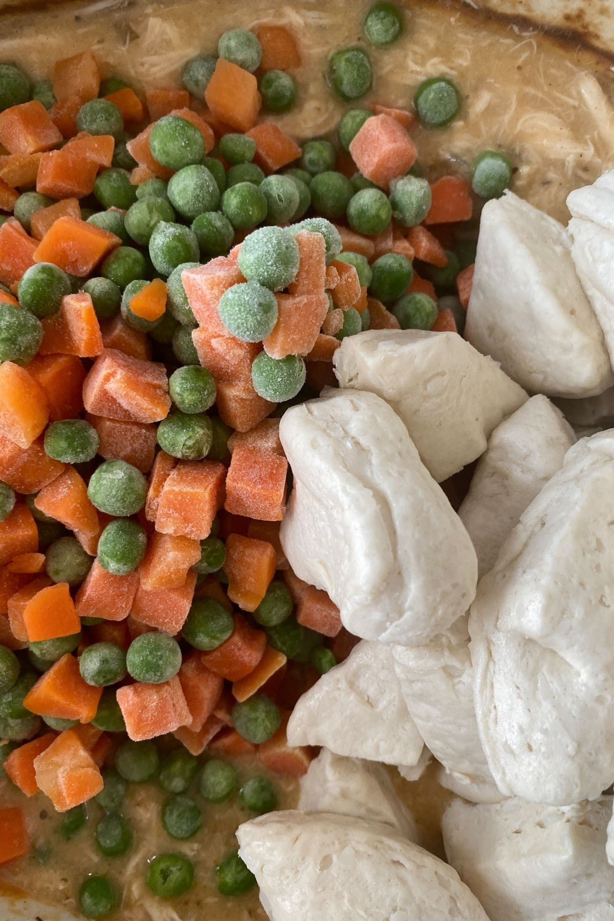 Peas and carrots on top of soup next to raw biscuits