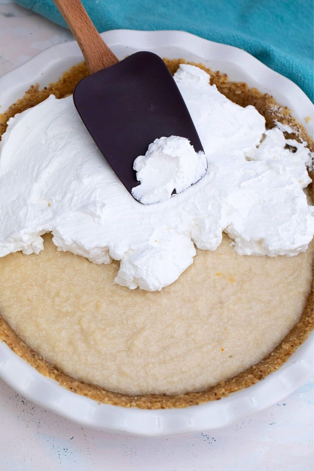 Spreading whipped cream over coconut filling