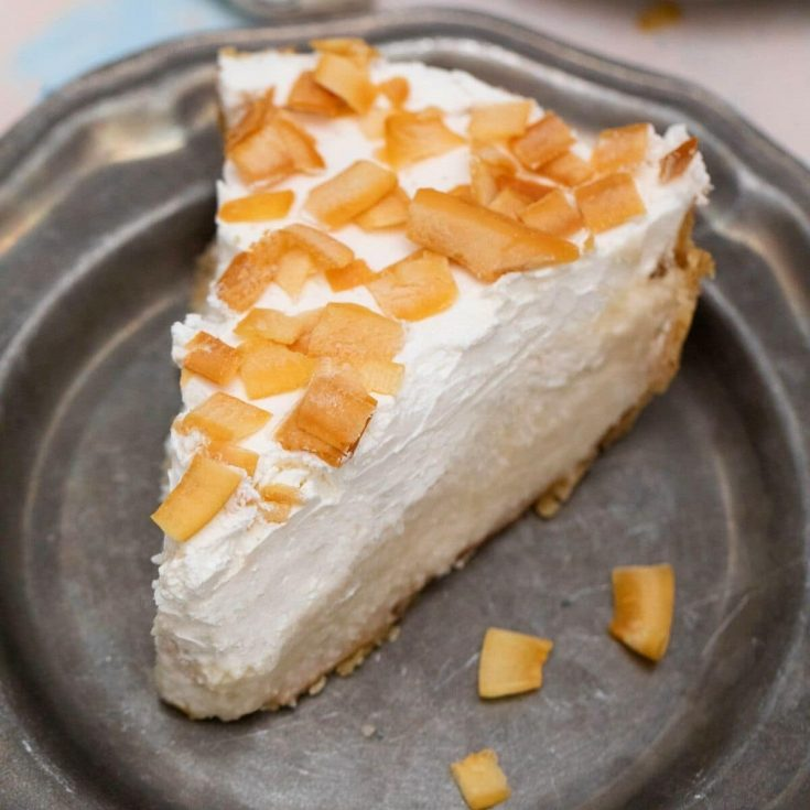 Coconut cream pie on black plate with teal napkin in background