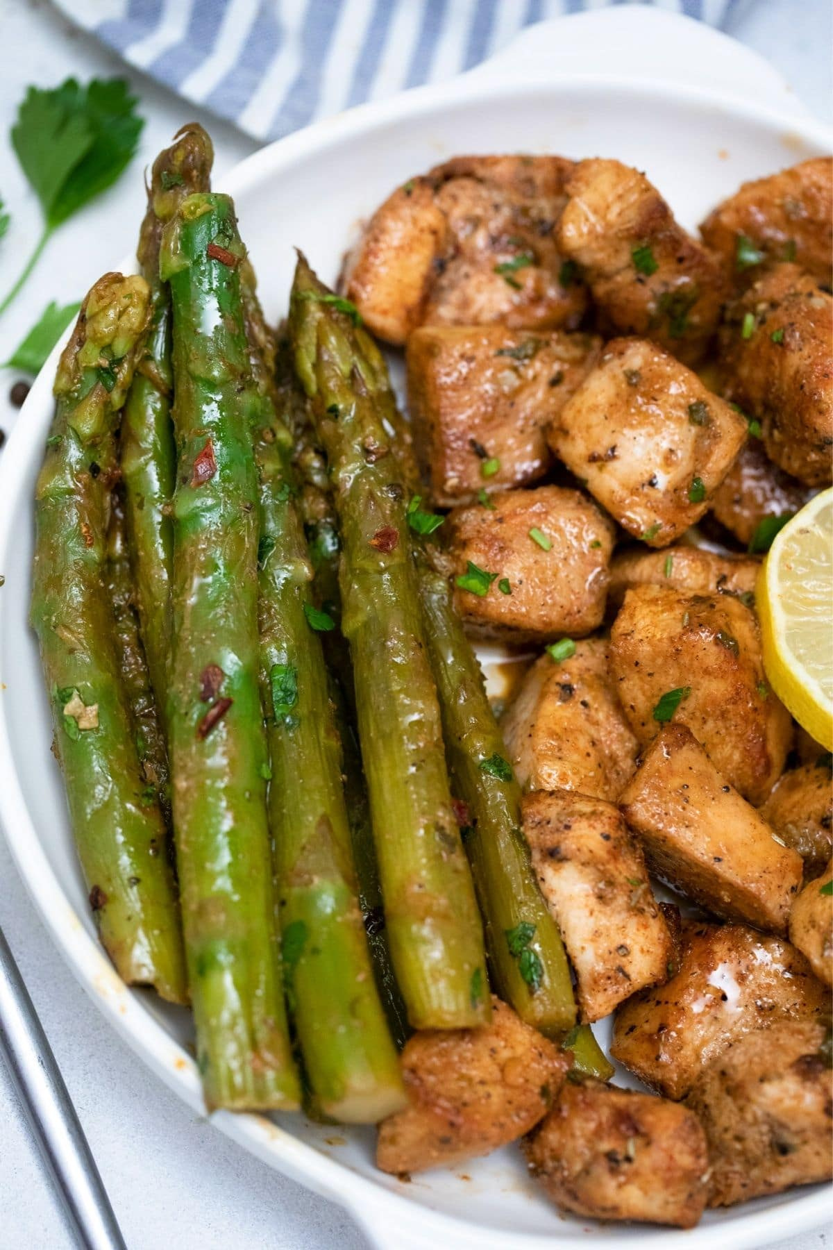 White plate with asparagus spears on left side and chicken on right