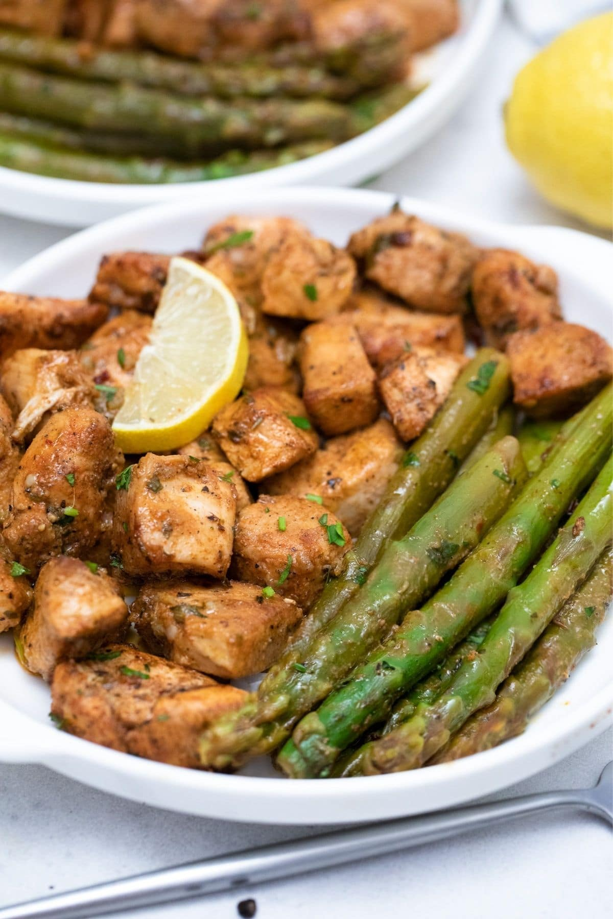 Chicken and asparagus on plate with lemon slice