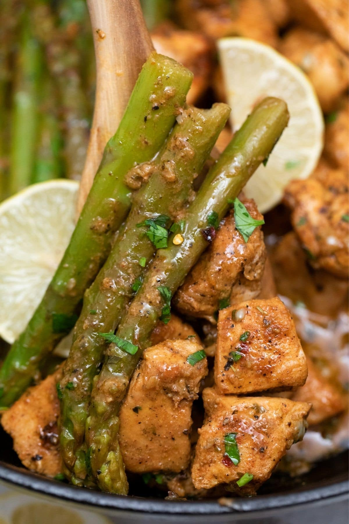 Wooden spoon holding asparagus and chicken