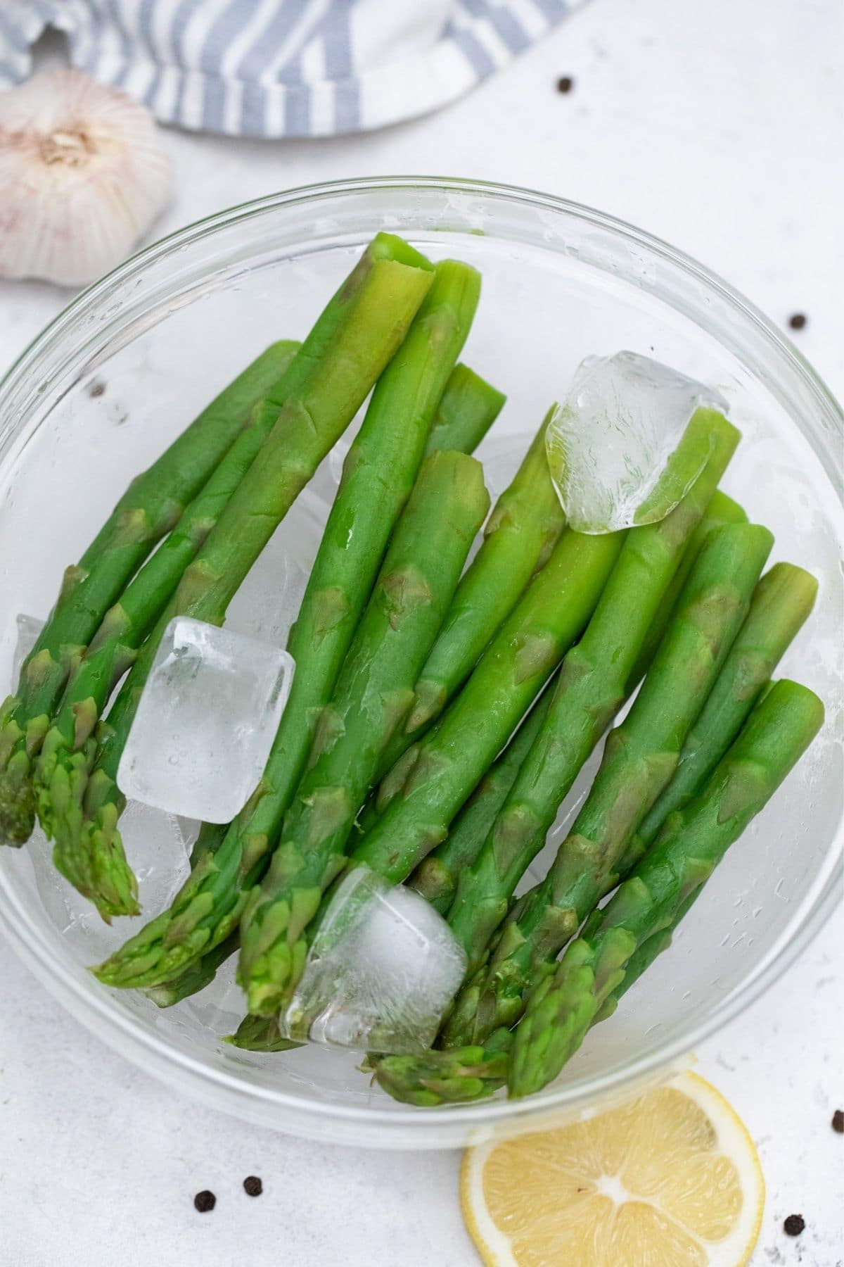Asparagus spears on ice in glass bowl