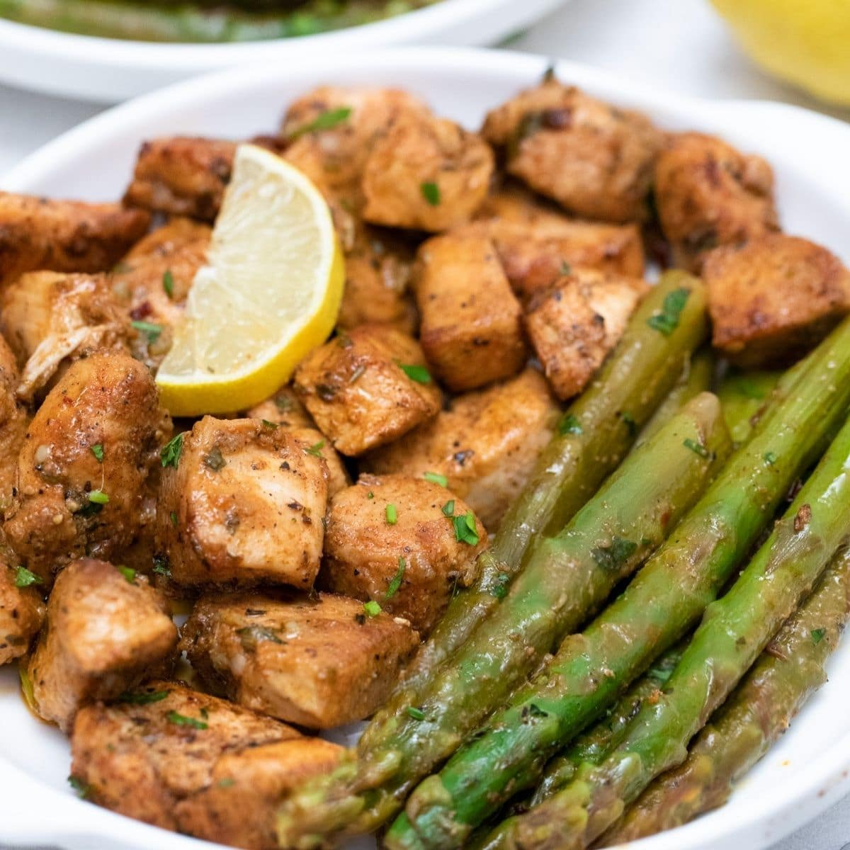 White plate with garlic butter chicken and asparagus