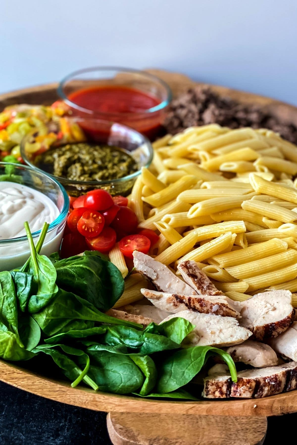 Charcuterie board with pasta chicken beef and three sauces