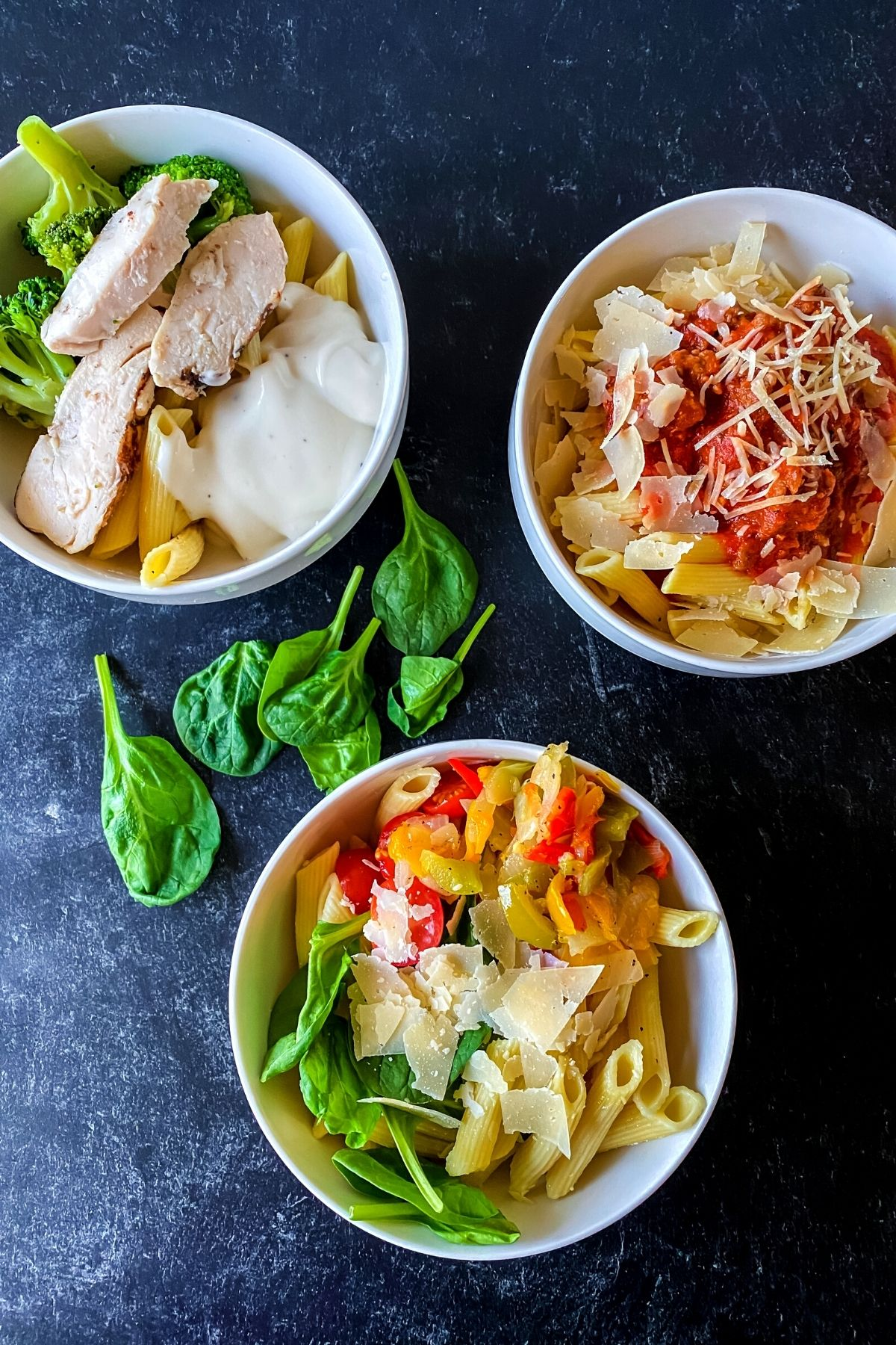 Three white bowls of pasta with different toppings
