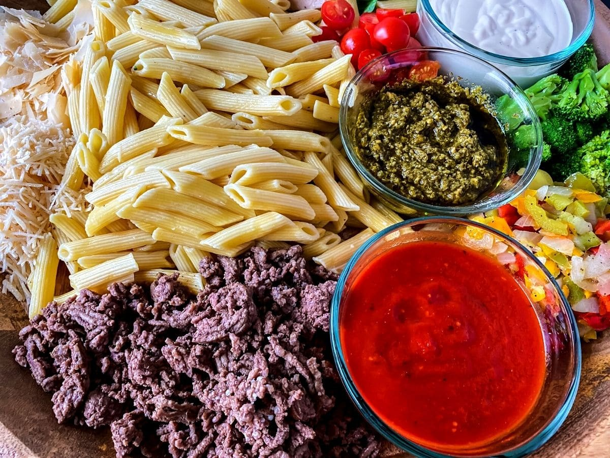 Penne ground beef tomato sauce and pesto on board