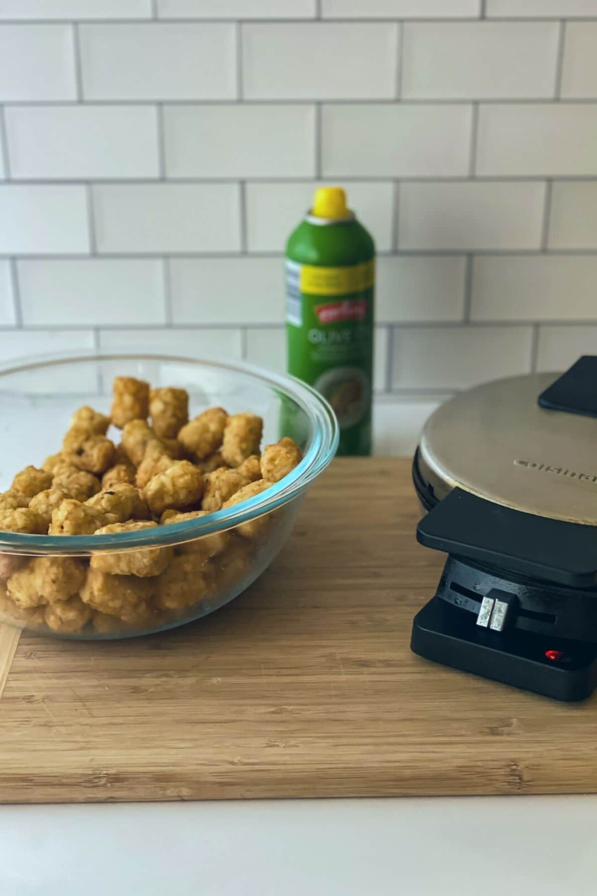 Tater tots in large glass bowl by cuisinart waffle aker