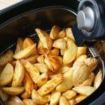 Air fryer potato wedges in black air fryer basket