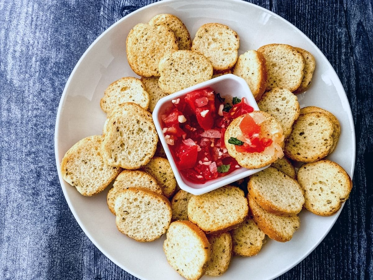 Bruschetta on white plate with bowl of tomatoes in center
