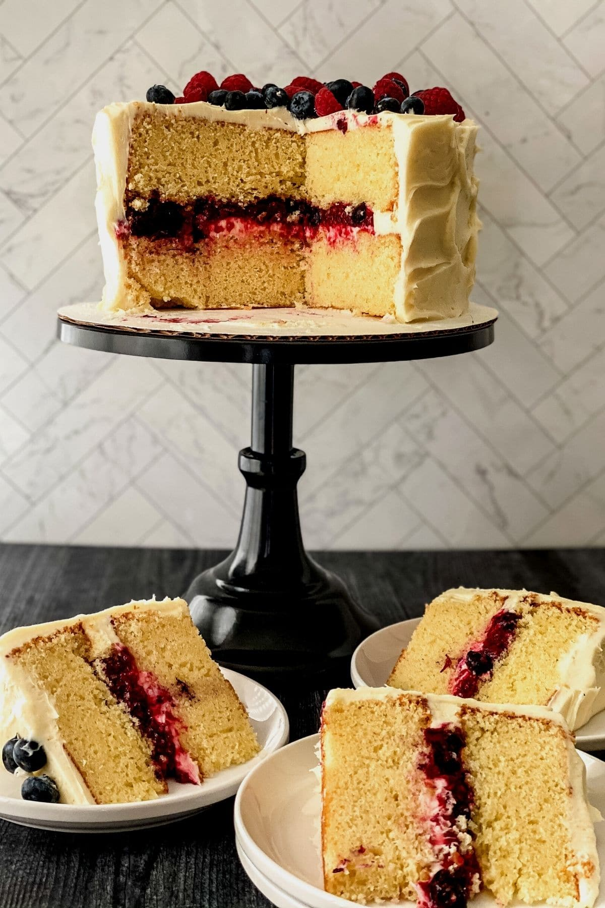Black cake stand with vanilla and berry layer cake