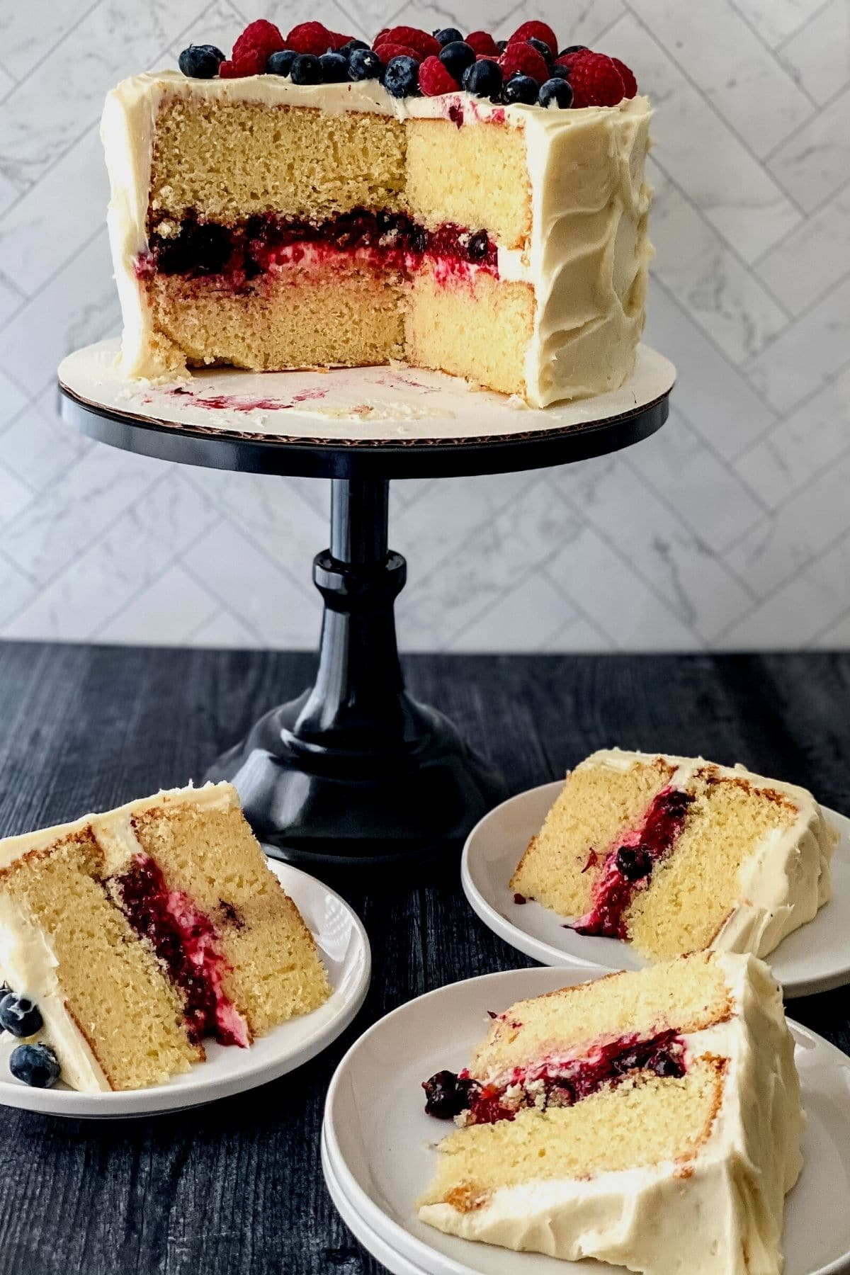 Berry layer cake on black cake stand with slices on plates