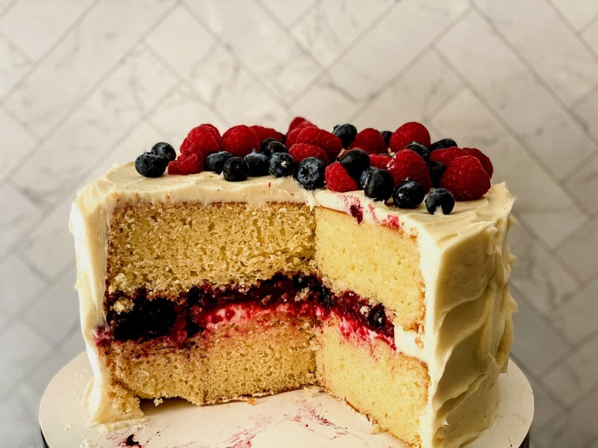 Chantilly berry layer cake on white cake stand