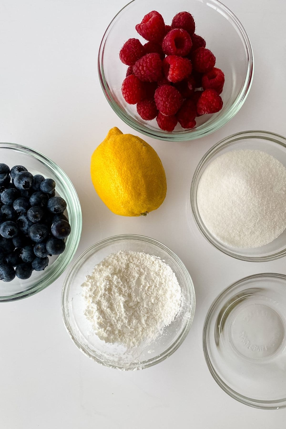 Ingredients for berry compote in glass bowls