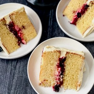 Slices of layer cake with berry filling on white plates