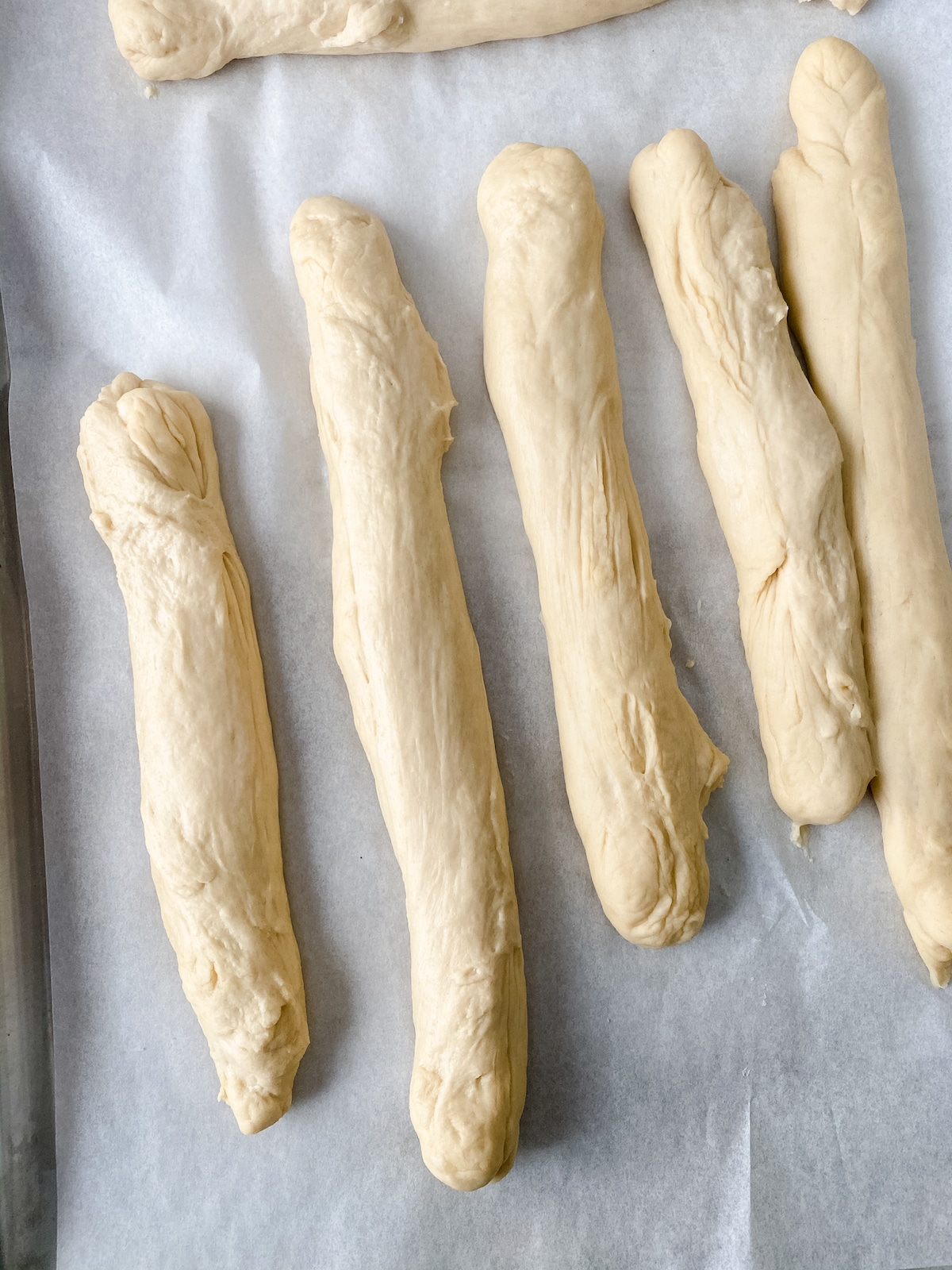 Rolls of pretzel dough on parchment paper