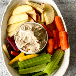 White bowl with vegetables and fruit surrounding a glass bowl of nutbutter dip