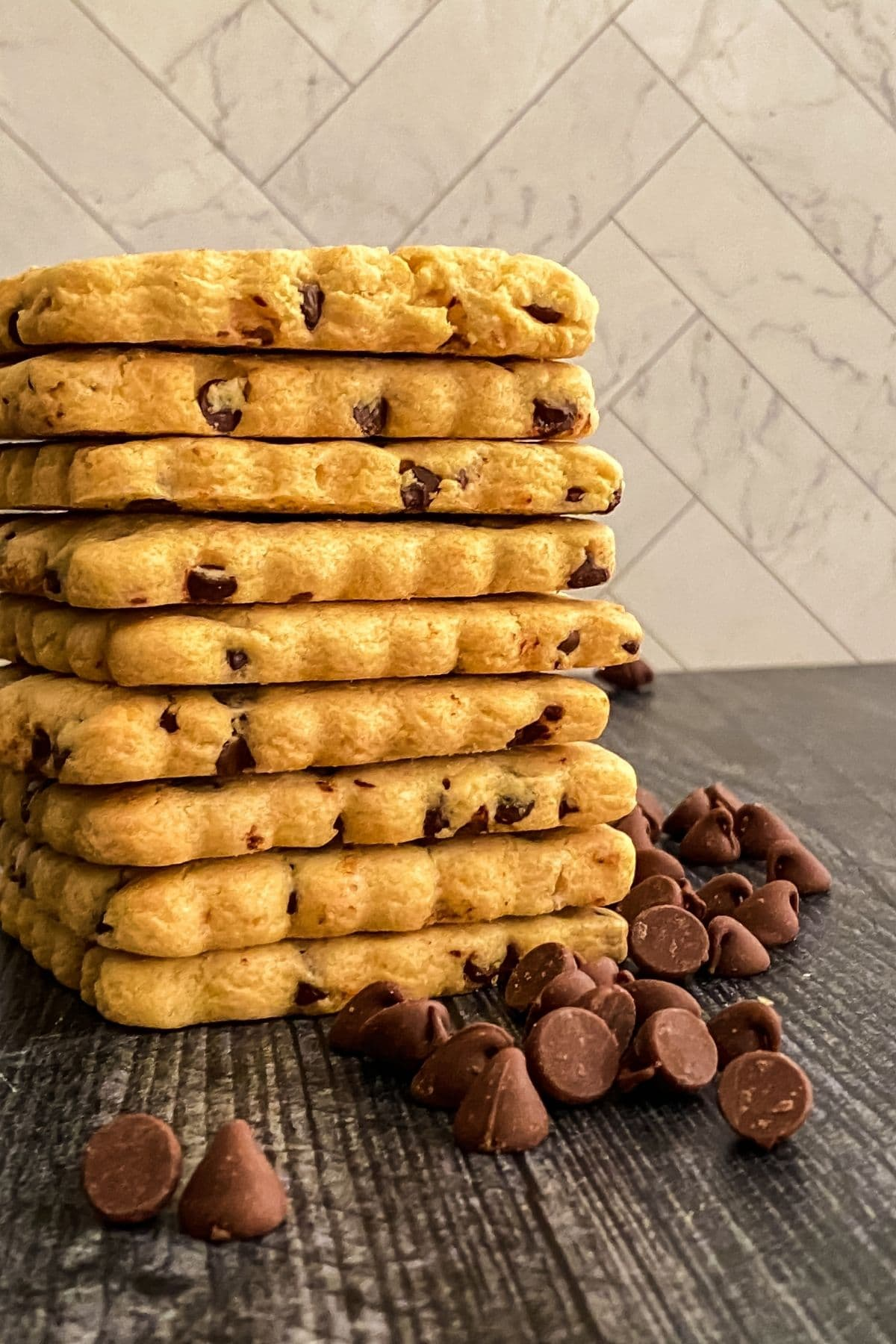 Stack of cookies on black table with chips beside