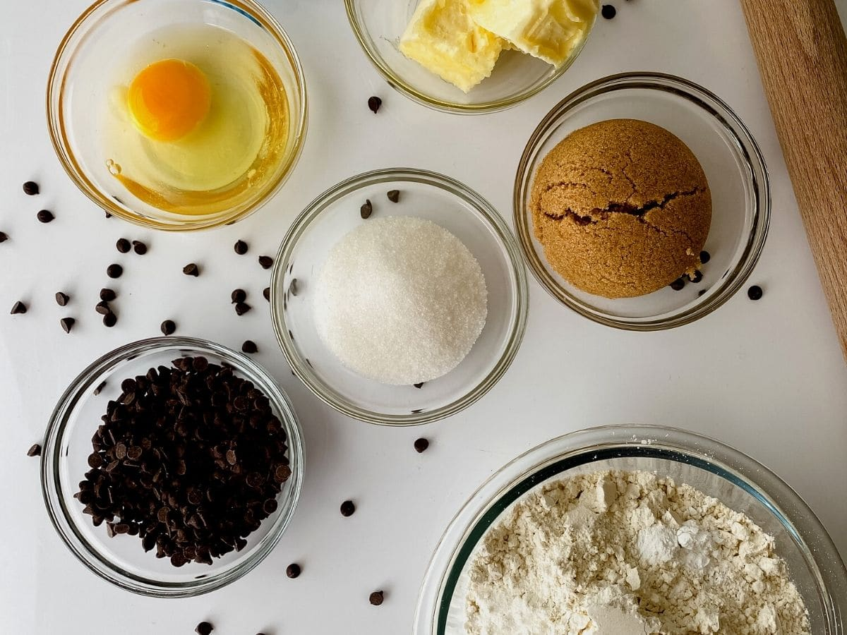 Ingredients for cut out cookies in glass bowls on white table