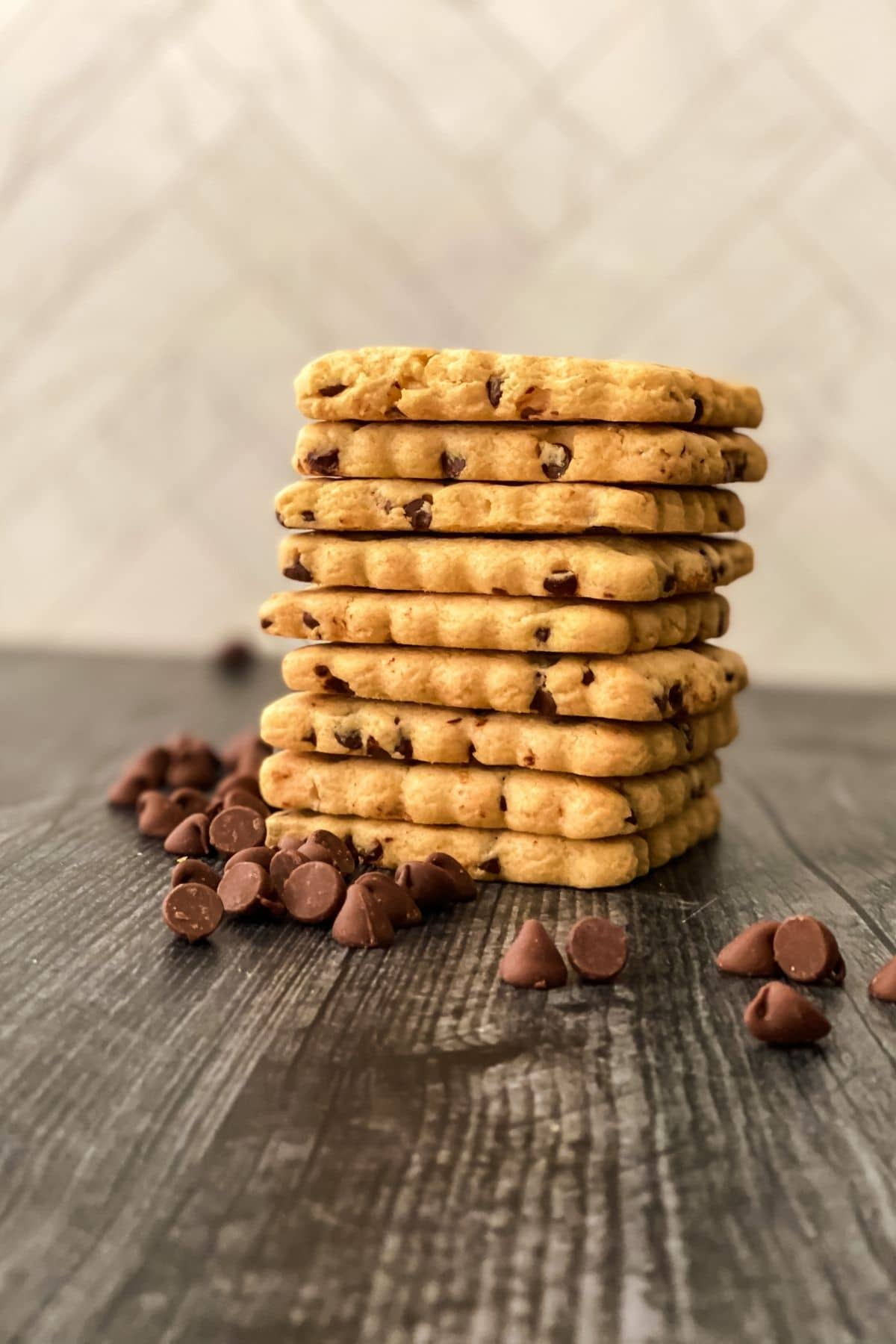 Short stack of cookies on table next to scattered chocolate chips