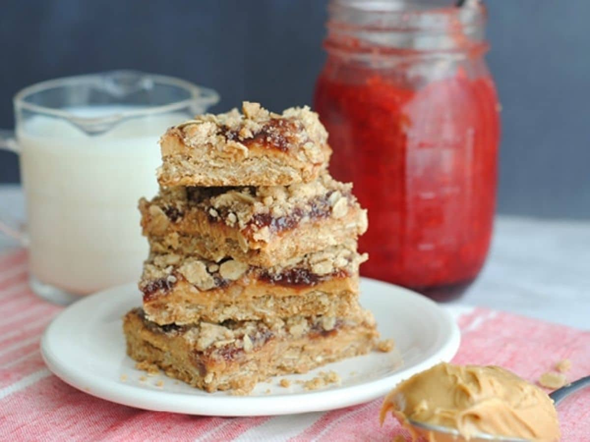 Peanut butter and jelly bars on white plate over pink napkin