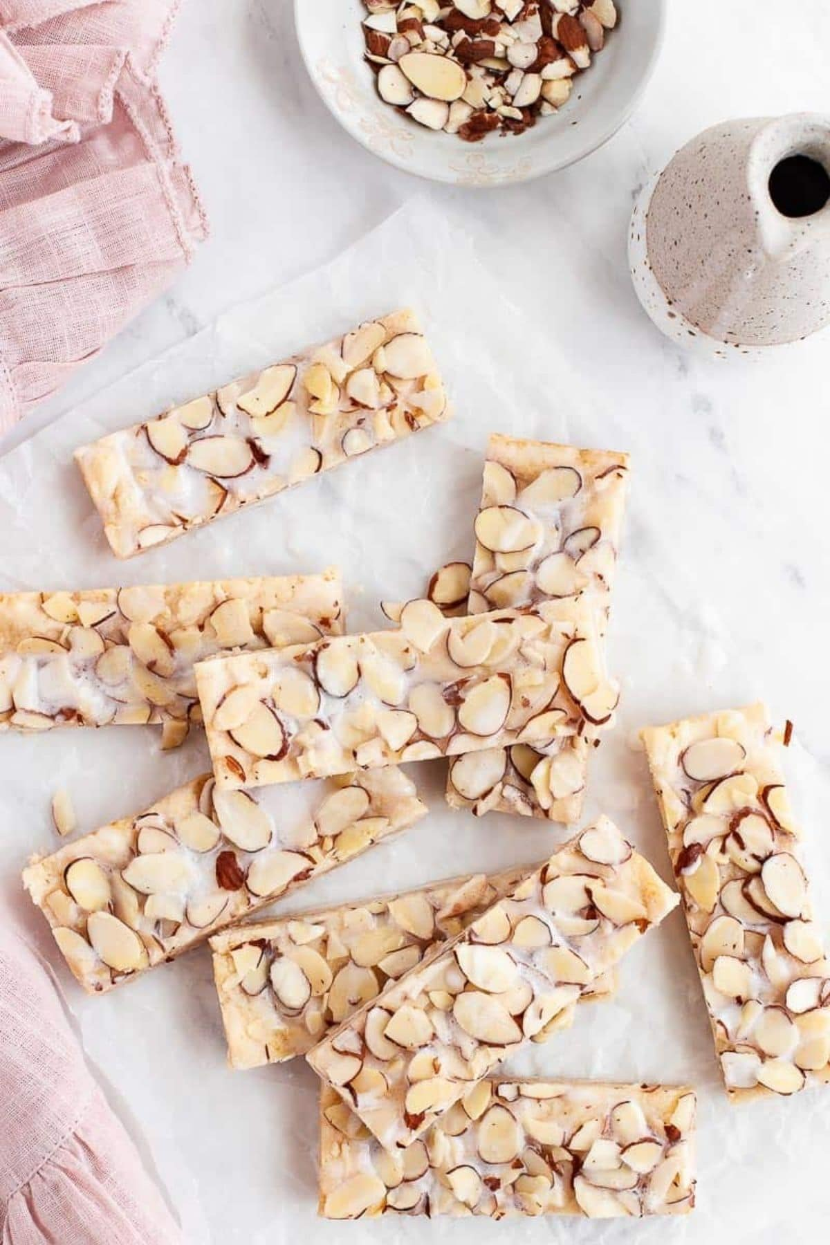 Almond bars cut into rectangles stacked on marble