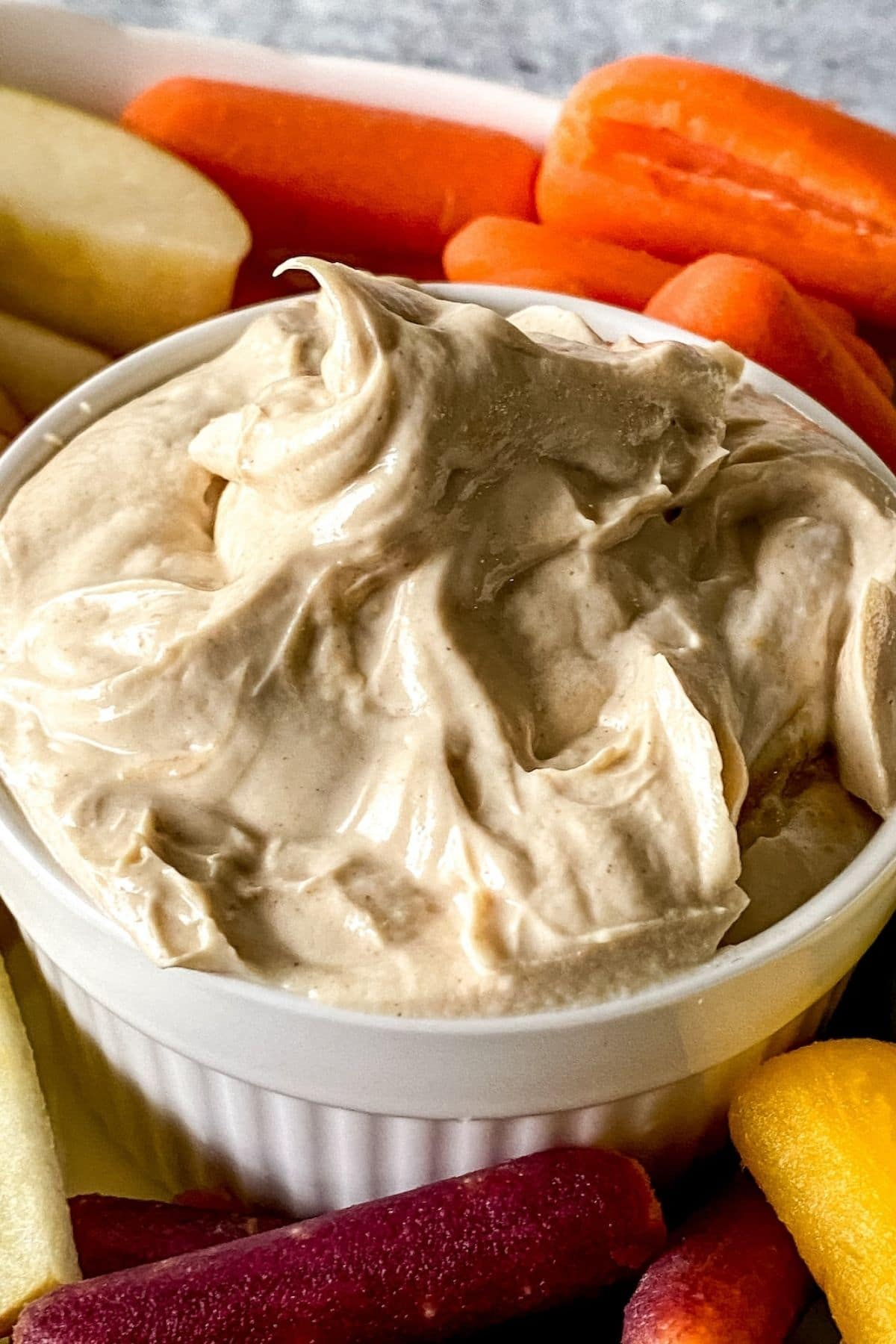 White ramekin filled with nut butter dip by carrots and apples